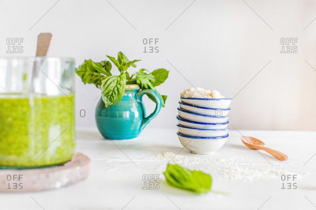 Ingredients for pesto next to fresh traditional basil pesto