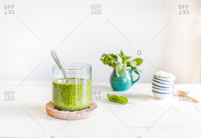 Fresh traditional basil pesto in a glass cup nest to basil and parmesan cheese