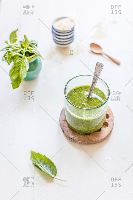 Glass container of fresh basil pesto sauce