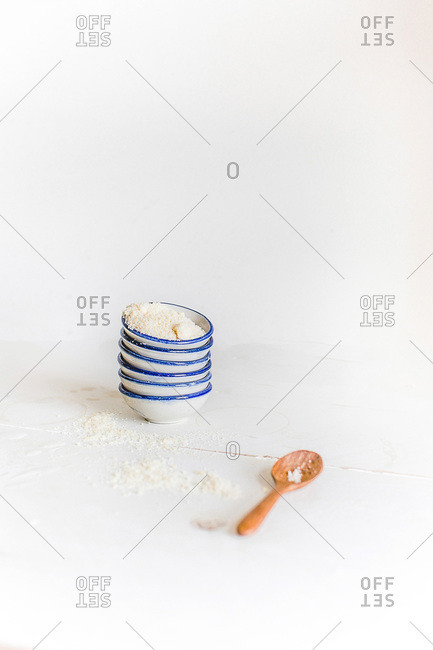 Six small bowls stacked with parmesan cheese and a wooden spoon