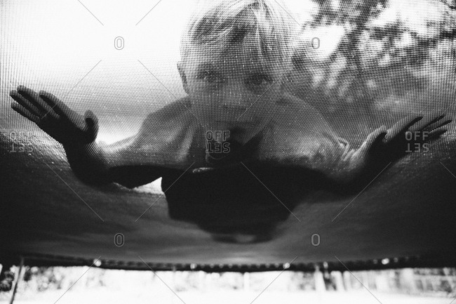 Child looking through trampoline