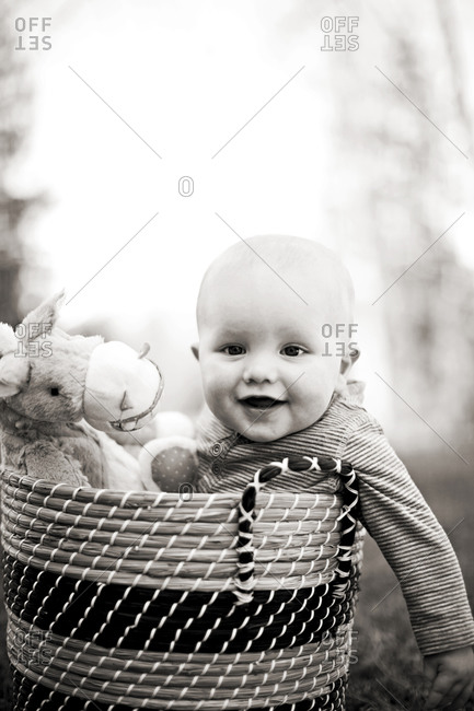 Baby in basket on ground