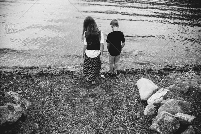 Two kids standing on lake shore