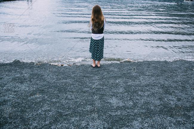Girl in dress on lake shore