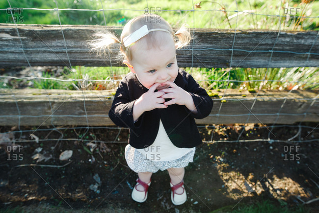 Toddler in dress by wood fence