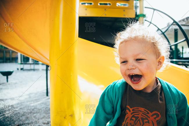 Smiling boy on bottom of slide