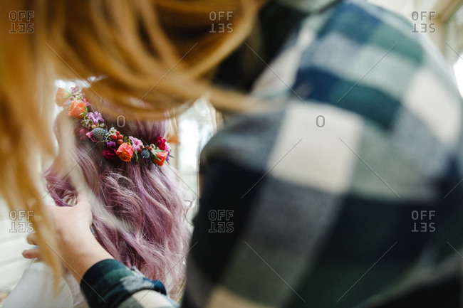 Woman setting friend's floral crown