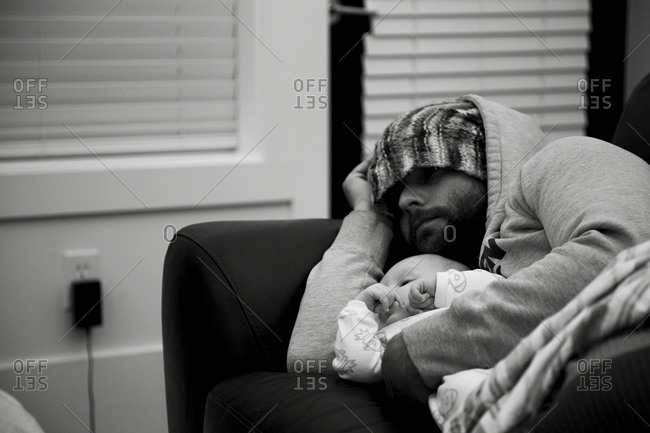 Dad cuddling baby on couch