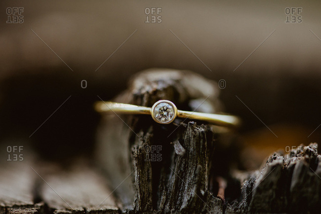 Close-up of a bezel set diamond ring on piece of  wood
