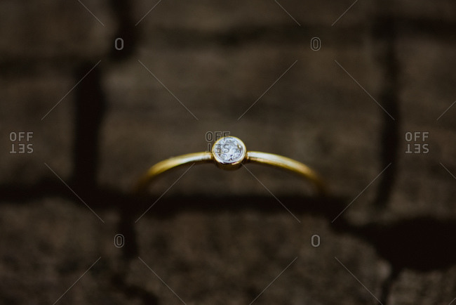 Close-up of a bezel set diamond ring in piece of  wood