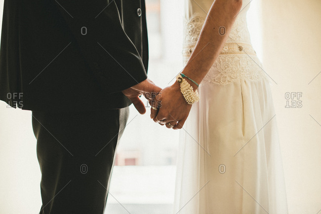 Close-up of a couple holding hands in their wedding attire
