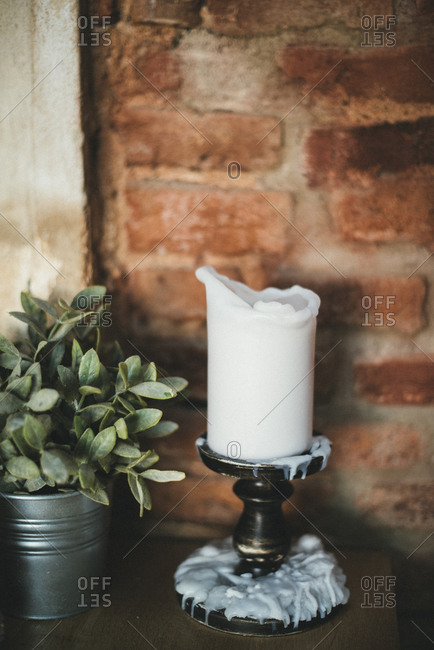 Candlestick with candle and white wax dripped over base