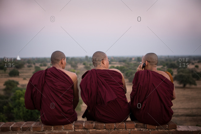Three monks sitting on a brick wall in Bagan, Myanmar
