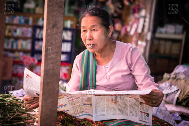 Inle lake, Myanmar - February 1, 2015: Asian woman smoking and reading a newspaper