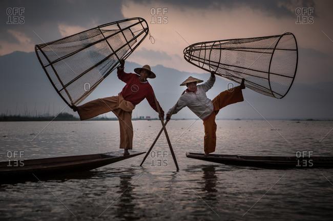 Inle lake, Myanmar - February 2, 2015: Two fishermen balancing on boats with nets