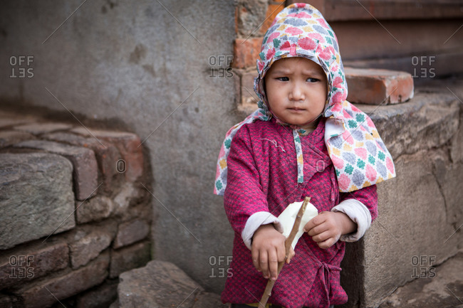 Bhaktapur, Nepal - April 14, 2015: Portrait of a little girl holding a stick
