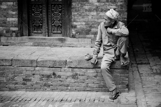 Bhaktapur, Nepal - April 14, 2015: Man sitting on a city street