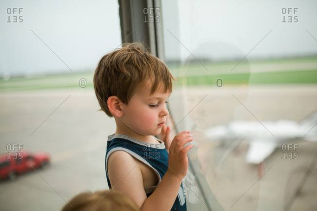 Little boy standing at the window of an airport observation tower