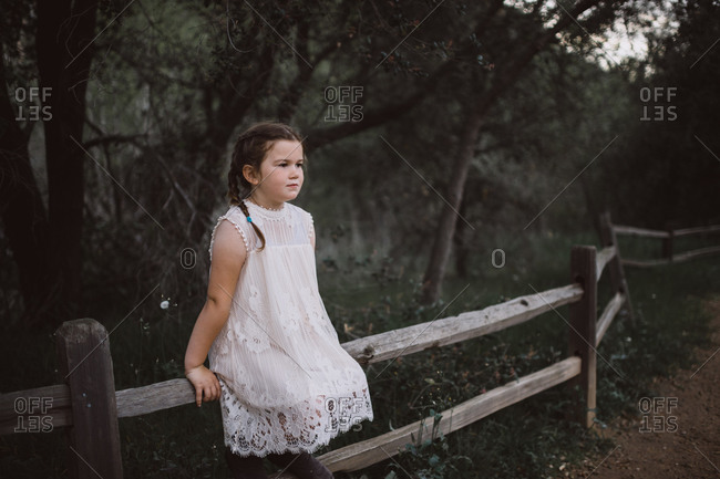 Little girl sitting on a fence beside a forest trail