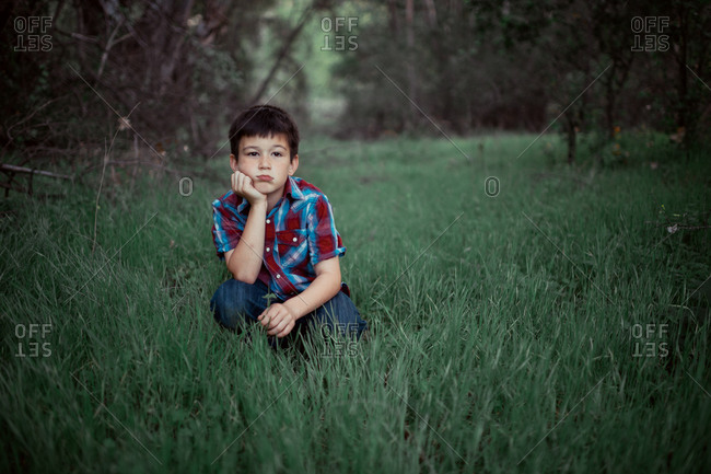 Little boy resting his chin in his hand in a grassy field