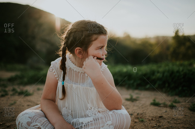 Little girl sitting on a dirt path playing with her hair