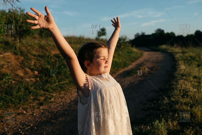 Little girl standing on a dirt path with her arms outstretched taking in the sun