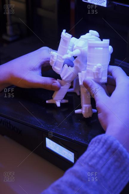 Hands taking a 3D robot figurine from a 3D printer