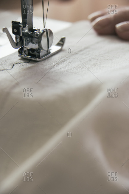 Sewing machine sewing on a white cloth
