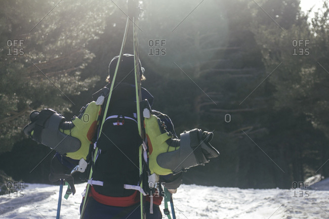 Backlighting of a man with skis in a backpack