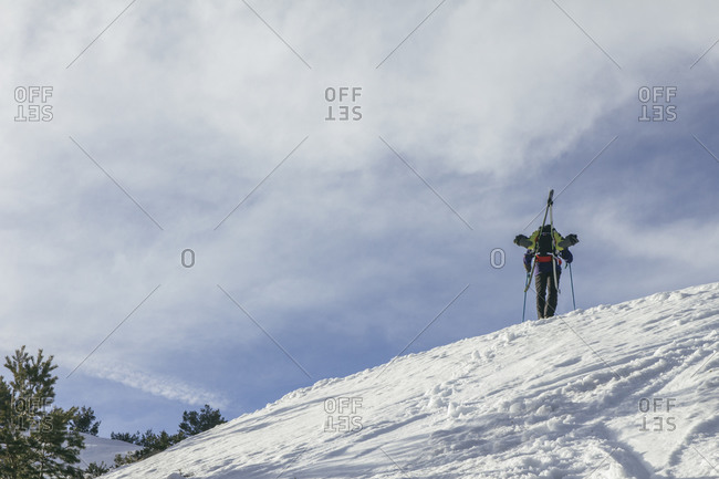 Spain, Man with skis in a backpack on top of a snowy hill, Penalara Mountain