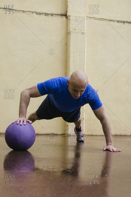 Man doing push-ups with a medicine ball