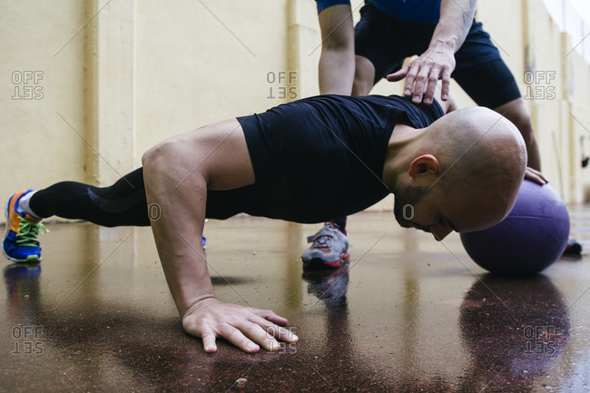 Man doing push-ups with a medicine ball assisted by a trainer
