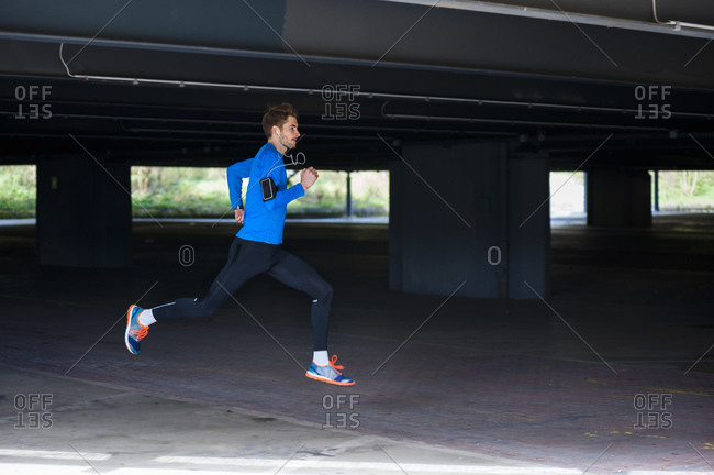 Young sporty man jogging with smartwatch and headphones