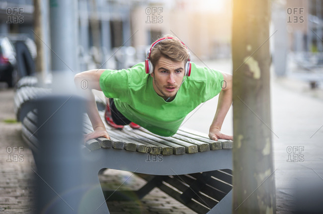 Young sporty man with headphones doing pushups on bench