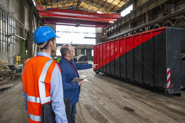 Manager and worker talking at container in factory hall