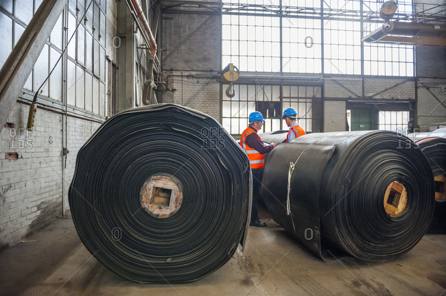 Two men with safety vests in factory hall with rolls of rubber