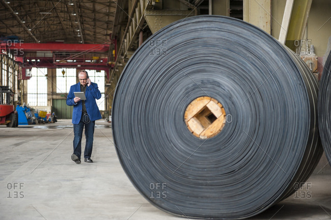 Manager with digital tablet in factory hall with rolls of rubber