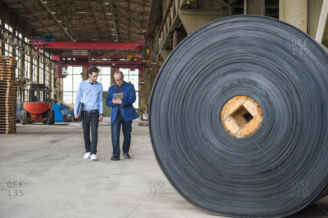 Two men walking in factory hall with rolls of rubber