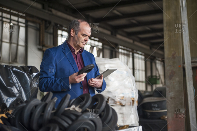 Manager with digital tablet in factory hall checking rubber product