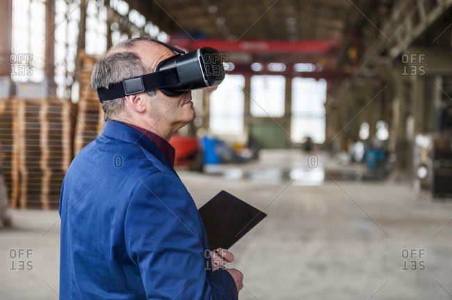 Manager standing in factory hall looking through VR glasses