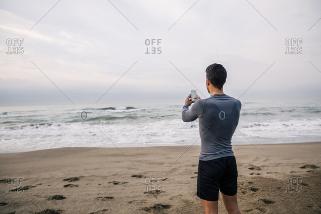 Sportive young man with cell phone on the beach