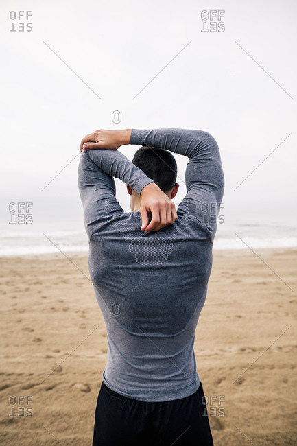 Sportive young man stretching on the beach