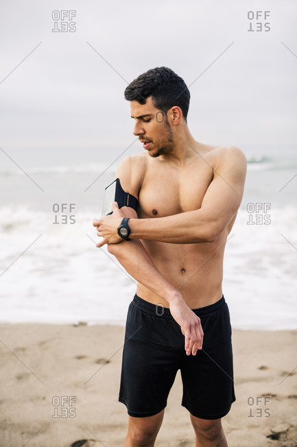 Sportive young man on the beach adjusting wearable