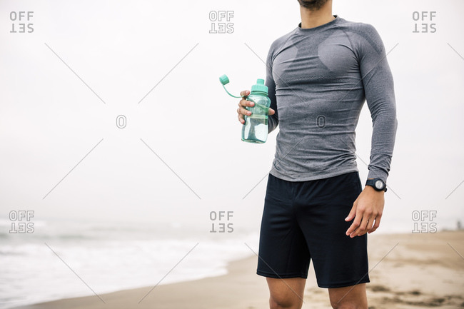 Sportive young man with drinking bottle standing on the beach