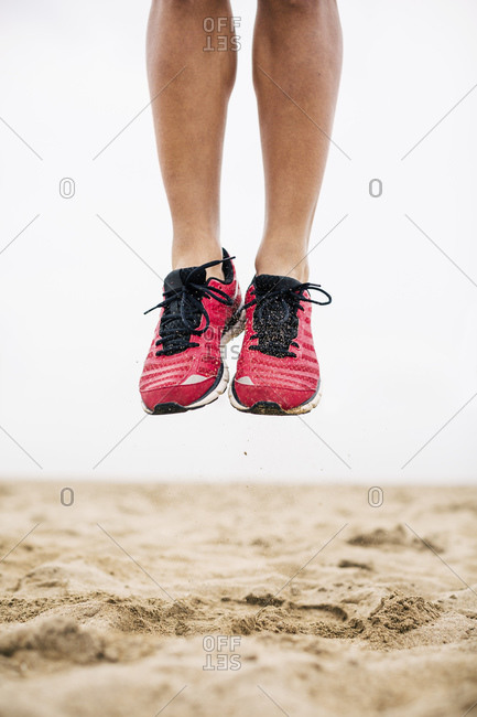 Legs of athlete jumping mid-air in sand