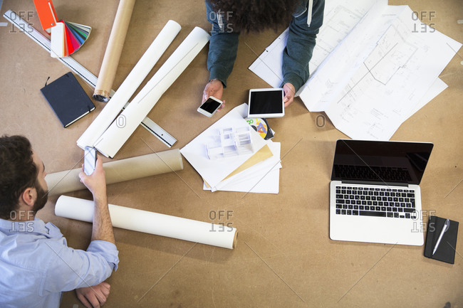 Two colleagues with portable devices surrounded by construction plans