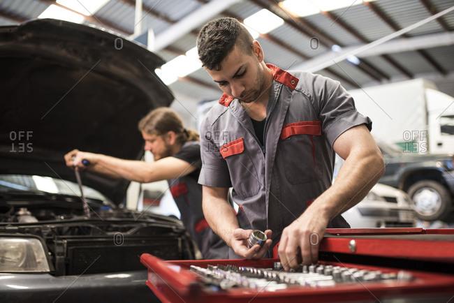 Men repairing engine car in workshop