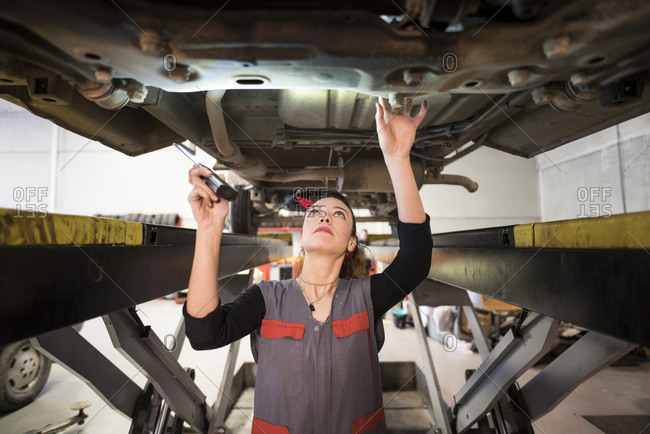 Mechanic woman working under a car with led light