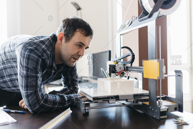 Worker controlling a model, 3D printer