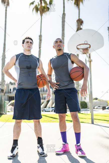 Two young men standing on outdoor basketball court